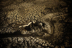 Sad dirty woman is at cracked earth desert Royalty Free Stock Photography