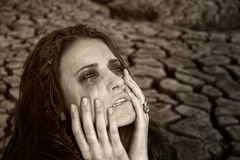 Sad dirty woman is at cracked earth desert royalty free stock images
