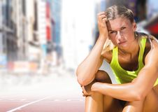 Sad disappointed athlete runner sitting down in city. Digital composite of Sad disappointed athlete runner sitting down in city Stock Image