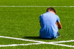 Sad disappointed boy sitting on the grass in stadium royalty free stock images