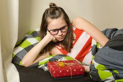 Sad disappointed teen girl looking at gift sitting in bed at home.  Royalty Free Stock Image