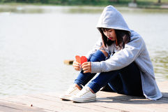 Sad and disappointed woman sits near river.  royalty free stock image