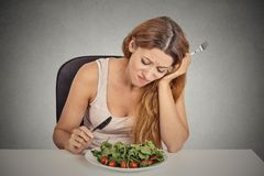 Sad displeased young woman eating salad. Isolated grey wall background. Negative human face expression emotion stock photos