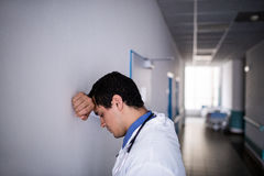 Sad doctor leaning against the wall. In hospital corridor stock photo