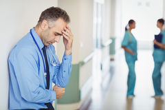 Sad doctor leaning against the wall Stock Photos
