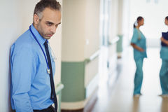 Sad doctor leaning against the wall Stock Photo