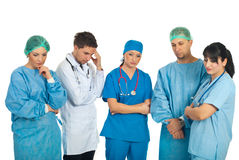 Sad doctors team. With problems standing in a row and thinking at solutions isolated on white background royalty free stock photo