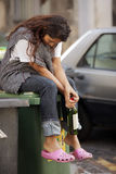 Sad drunk homeless woman. Drunk homeless woman sitting on bin and holding botle of wine stock photography