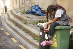 Sad drunk homeless woman on bin. Drunk homeless woman sitting on bin and holding botle of wine royalty free stock photos