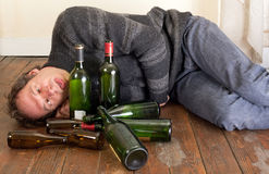 Sad and drunk man. Drunk man lying on floor with empty bottles Royalty Free Stock Photography