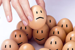 Sad egg. An egg selected among others, feeling sad stock photo