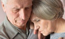 Sad elder couple. Close-up portrait of cute sad elder couple royalty free stock images