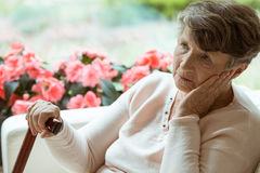Elder lady worrying. Sad elder lady sitting on the sofa and worrying about her health stock photography