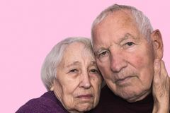 Sad elderly couple on a gray background stock images