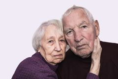 Sad elderly couple on a gray background royalty free stock images