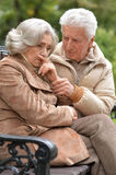 Sad elderly couple sitting on a bench in autumn park. Portrait of a sad elderly couple sitting on a bench in autumn park Royalty Free Stock Photos