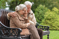 Sad elderly couple sitting on a bench in autumn park. Portrait of a sad elderly couple sitting on a bench in autumn park Stock Photos