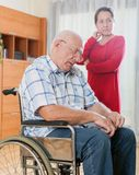 Frustrated wife next to elderly husband in wheelchair. royalty free stock photography