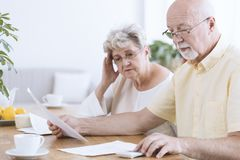 Sad elderly marriage with documents. Sad elderly marriage sitting with documents and calculator at a table with coffee stock image