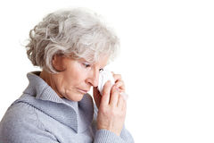 Sad elderly woman. Old senior woman crying and drying her tears with a handkerchief Royalty Free Stock Photo