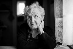 An sad elderly woman, black-and-white portrait. Royalty Free Stock Photo