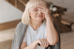 Sad elderly woman closing her eyes. I am so exhausted. Sad pleasant elderly woman closing her eyes and touching her forehead while feeling tired Stock Photography