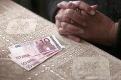 Sad elderly woman with euro notes on table toned image selective focus shallow dof Royalty Free Stock Photography