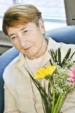 Sad elderly woman with flowers Royalty Free Stock Photos