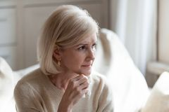 Upset senior woman sorrow for something at home. Sad elderly woman looking in distance thinking about life difficulties, thoughtful senior female feel lonely stock images
