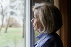 Sad elderly woman. Looking out the window stock photo