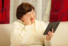 Sad elderly woman looking at photo frame stock photography