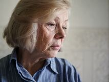 Sad elderly woman. With lowered eyes stock images