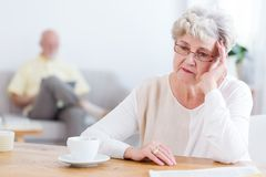 Sad elderly woman sitting at a wooden table, thinking about divo royalty free stock photography