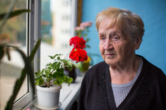 Sad elderly woman stands on her balcony. Loneliness. Stock Photography