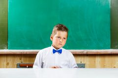 Sad or embarrassed school boy at the blackboard Stock Photography