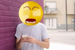 Sad emoji head man. Using a smartphone. Emoji concept stock images