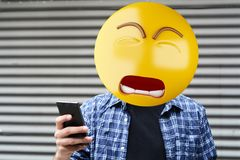 Sad emoji head man. Sad Emoji head man using a smartphone. Emoji concept royalty free stock images
