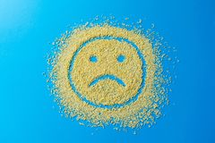 Sad emoji smile on a blue background. Smiley from yellow sugar grains. Stock image. royalty free stock images