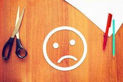 Sad emoticon made of paper on the desk Royalty Free Stock Photo