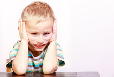 Sad emotional blond boy child kid at the table. Portrait of sad unhappy blond boy or child kid making silly funny face at the table interior. Emotions Royalty Free Stock Images
