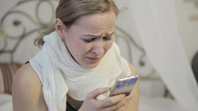 Sad, emotional woman crying and sends a message on mobile phone. She sitting on a bed in a bedroom stock video footage
