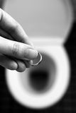 Sad Ending. Devastated woman throws her wedding ring in the toilet after divorce Royalty Free Stock Photos