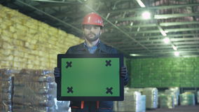 Sad engineer with chromakey sign. Angry or unhappy engineer worker in uniform in warehouse standing and holding a pad for copy space. Horizontal indoors shot stock footage