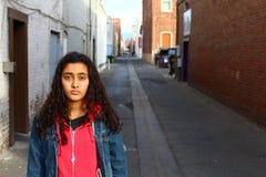 Sad ethnic teen girl outside stock photography