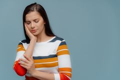 Sad European woman touches cheek, smirks face, has toothache, cant stand painful feelings, has long hair, dressed in striped. Jumper, models over blue royalty free stock images