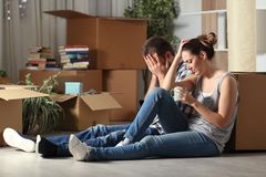 Sad evicted couple moving home complaining on the floor. Sad evicted couple moving home complaining sitting on the floor in the night royalty free stock images