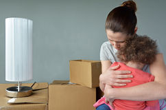 Sad evicted mother with child worried relocating house. Sad evicted mother (age 30-35) with child (age 2-3) worried relocating house.  Moving house concept. Real Stock Photography