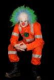 Sad Evil Clown. Sad, evil clown in safety orange costume on black background royalty free stock photo