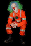 Sad Evil Clown. Sad, evil clown in safety orange costume on black background stock photography