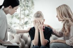 Sad exhausted girl sitting and crying. Family problem. Sad exhausted depressed girl sitting on the sofa between two women hiding her face and crying Stock Photo